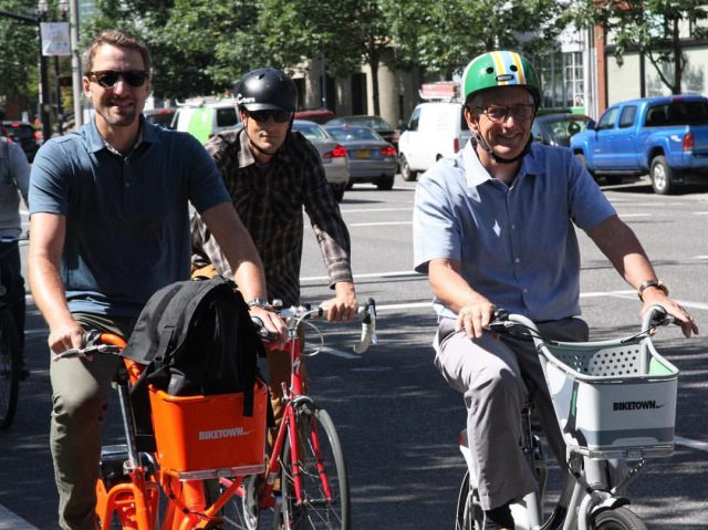 Mayor Hales (right) riding a Biketown bike on Naito Parkway this morning. (Photo: City of Portland)