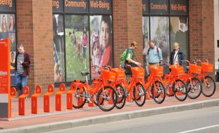 Passersby check out the Biketown bikes in the station at SW 5th and Oak.(Photo: J. Maus/BikePortland)