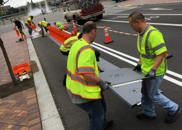 Crews are working overtime to get the final stations installed. This crew worked fast on Salmon Street on Saturday.(Photo: J. Maus/BikePortland)