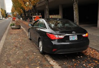 This Uber driver is parked illegally and is creating a dangerous situation by parking in a cycling-only lane on NE Multnomah.(Photo: J. Maus/BikePortland)