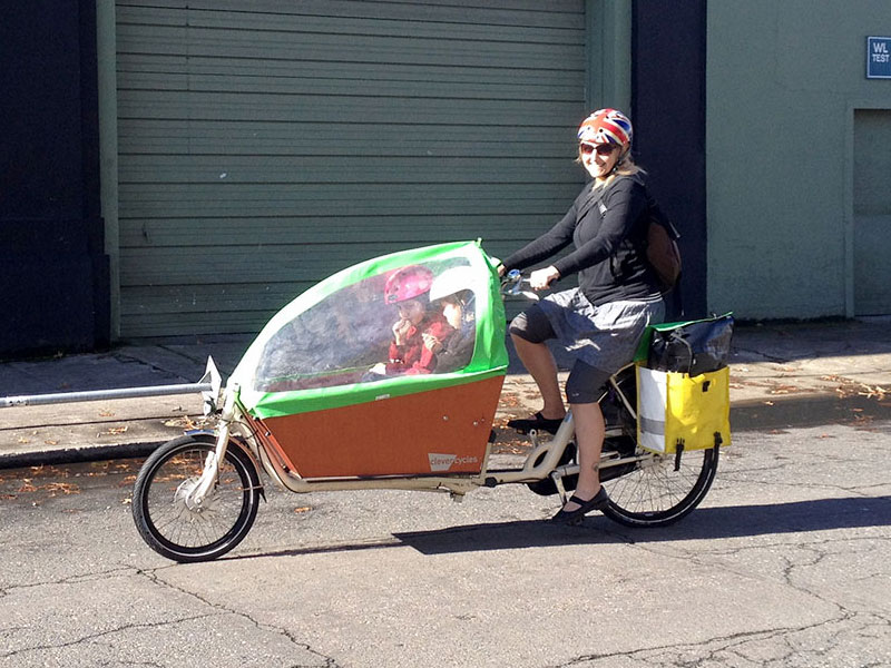 A bakfiets with canopy keeps passengers comfy.
