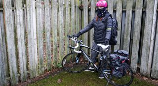 female cyclist standing in wet weather gear with bike